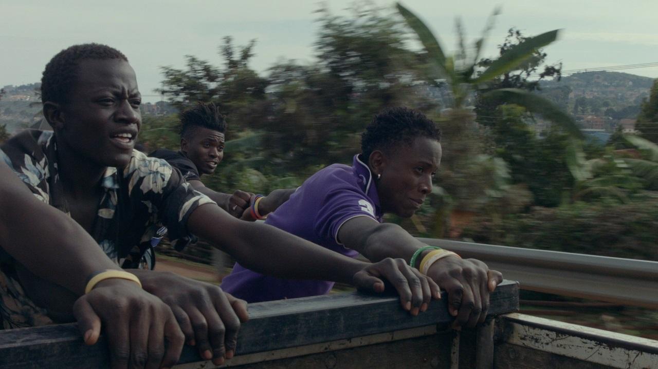 """Vier junge schwarze Männer fahren auf der Ladefläche eines Trucks mit. Filmstill aus """"Bloom""""."""