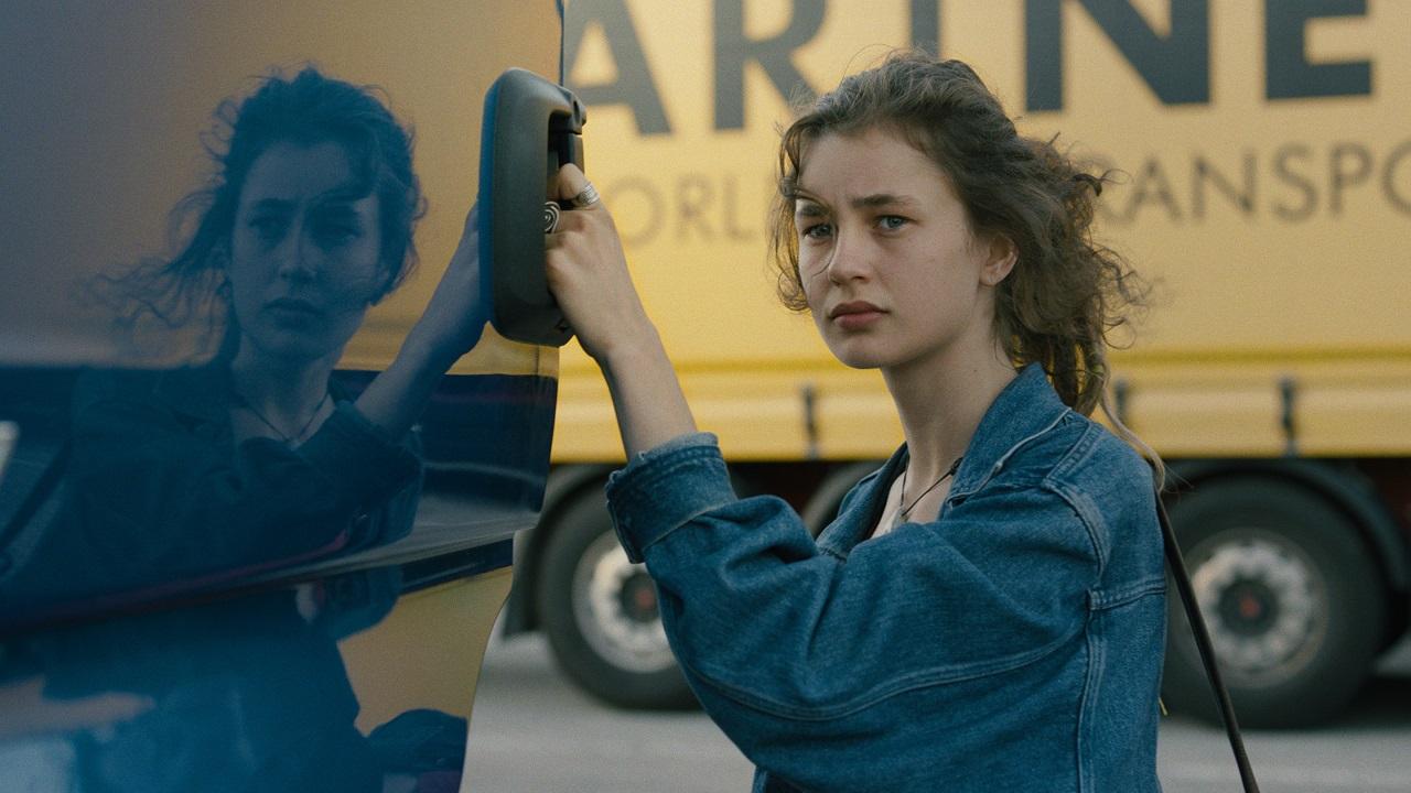 """Eine junge Frau hält sich an einem Lastwagen-Türgriff fest und schaut verzwickt. Szene aus dem Kurzspielfilm """"Favoriten""""."""