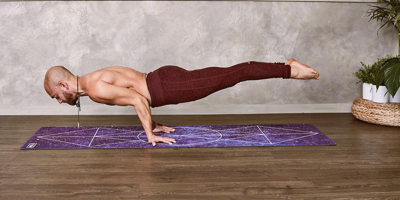 Mann macht Handstand auf Yogamatte