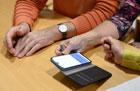 Hände von drei Personen mit einem Handy auf einem Tisch