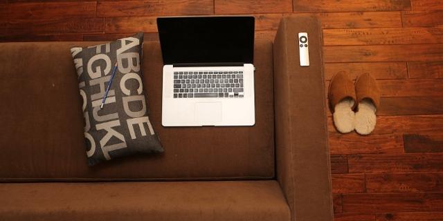 Sofa, Laptop, Hausschuhe, Fernsteuerung, von oben fotografiert