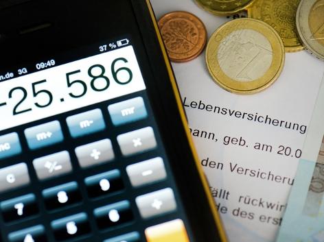 Auf einem Versicherungsschein für eine Lebensversicherung liegt ein Taschenrechner, sowie mehrere Euromünzen und ein Euroschein