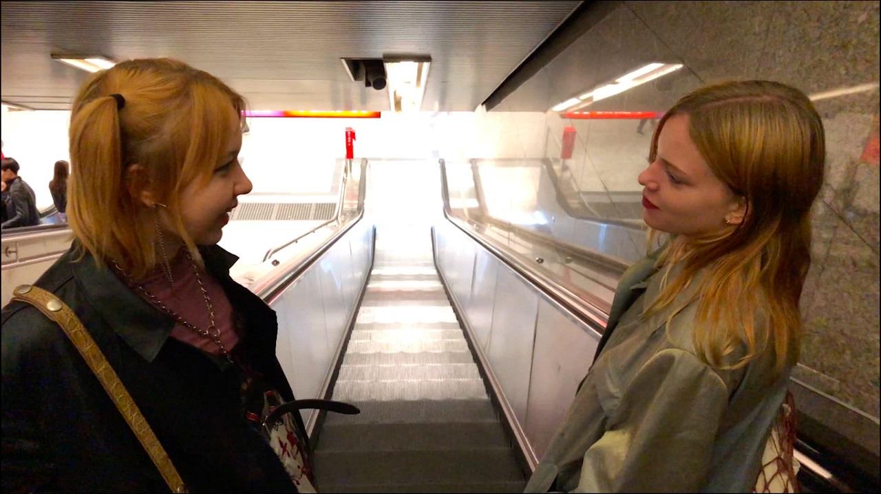 """Zwei junge Frauen stehen auf einer Rollstreppe und lächeln einander an. Filmstill aus """"Lololol""""."""