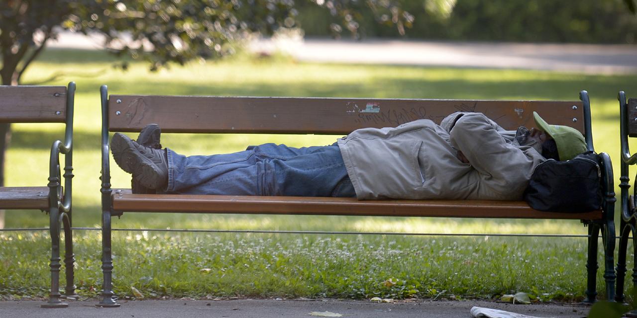 Mann liegt auf einer Parkbank und schläft