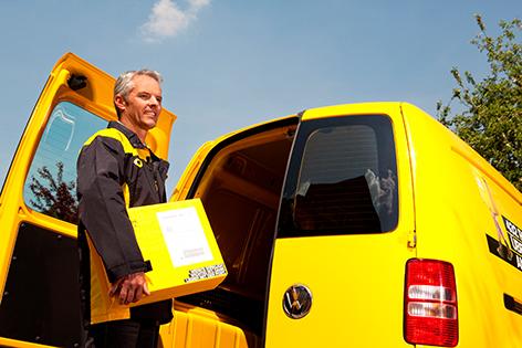 Ein Zusteller der Post legt ein Paket in den Lieferraum seines gelben Wagens
