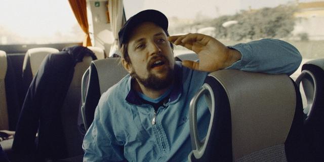 """Robin sitzt in einem Reisebus und ruft seiner Mannschaft etwas zu. Szene aus der Dokumentation """"Robin's Hood""""."""