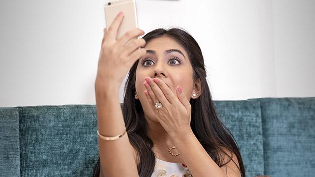 Frau schaut entsetzt aufs Handy