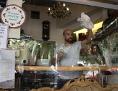 Ein Mann putzt von innen die Scheibe eines koscheren Geschäfts