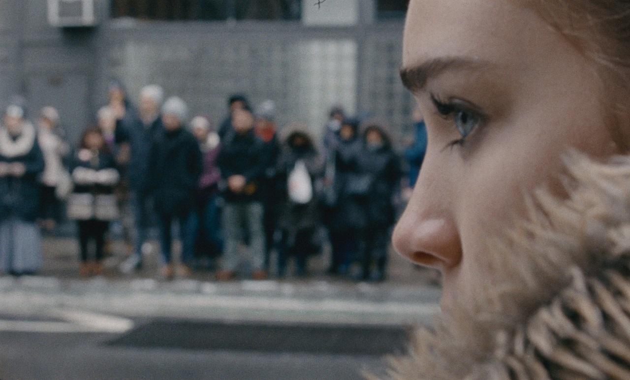 """Ein Mädchen steht auf der Straße und schaut, auf der anderen Straßenseite ist eine Gruppe von Demonstranten. Filmstill aus """"Never rarely sometimes always""""."""