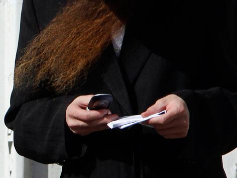 Ein orthodoxer Jude mit Smartphone