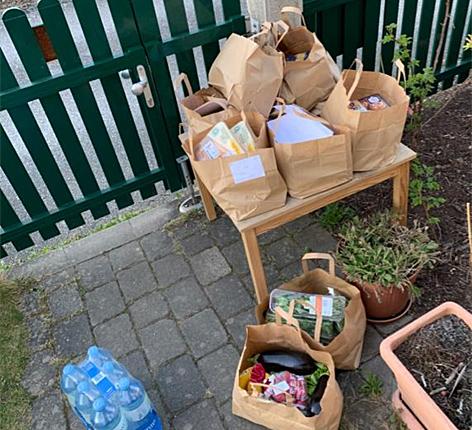 Eine Gartentür und viele gefüllte Papiersackerl mit Lebensmitteln auf einem kleinen Tisch hinter dem Gartenzaun