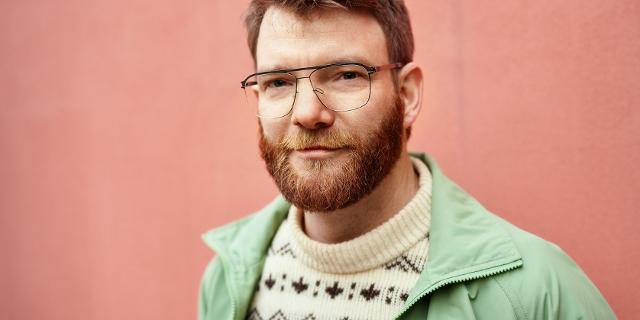 Der Autor Benjamin Maack trägt eine Jacke und Brille und steht vor einer Hauswand im Freien.