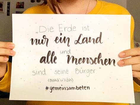 """Ein von einer Person gehaltenes Schild mit einem Spruch von Bahaullah: """"Die Erde ist nur ein Land und alle Menschen sind seine Bürger""""."""