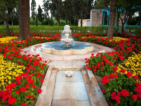 """Ein Brunnen mit blühenden Blumen rundherum im """"Paradiesgarten"""" der Baha'i bei Akkon in Israel"""