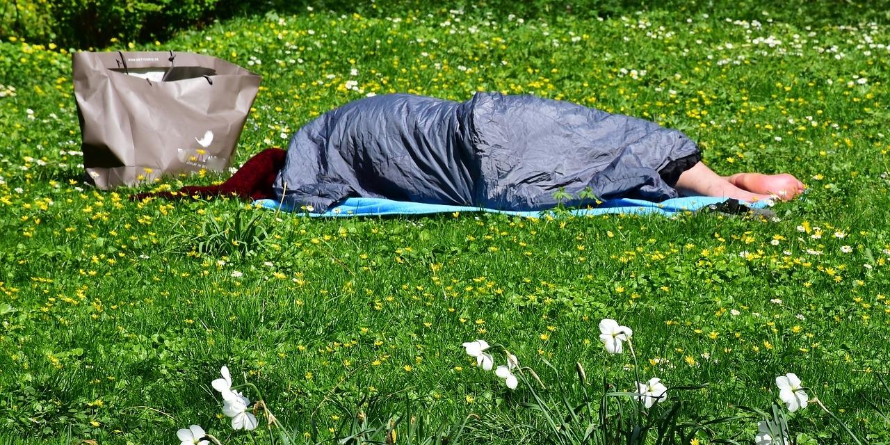 Obdachlose Person schlafend auf einer Wiese