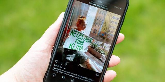 """Handy mit Foto: Frau am offenen Fenster ihrer Wohnung hält ein Plakat mit der Aufschrift """"Netzstreik fürs Klima"""""""