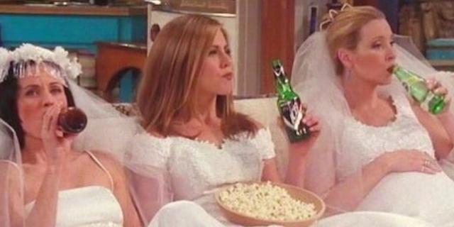 Sitcom Friends, Monika, Phoebe und Rachel sitzen in Hochzeitskleidern auf der Couch und trinken Bier