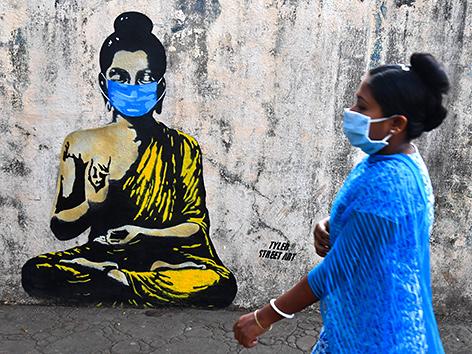 Vesakh: Eine Frau mit Maske geht an einem Graffiti vorbei, das Buddha mit Maske zeigt (Mumbai, Indien)