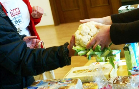 Team Österreich Tafel - Mitglied übergibt einen Blumenkohl bei der Essensübergabe