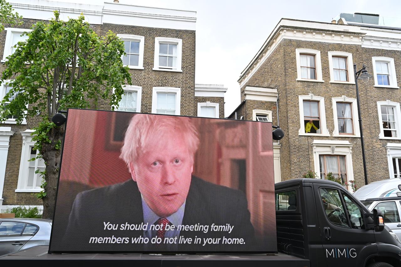Boris Johnson auf einem großen Bildschirm, der die Bevölkerung aufruft, niemanden zu treffen außer die Menschen im eigenen Haushalt.