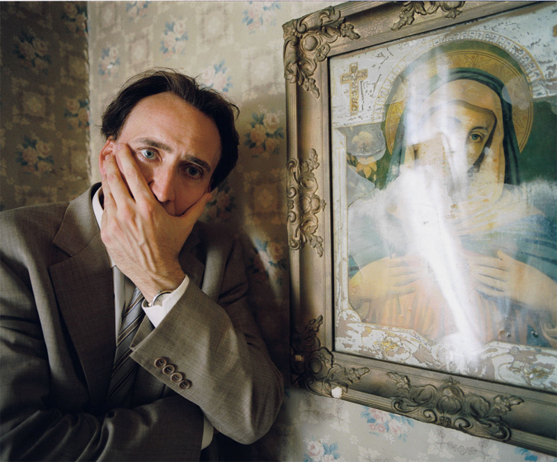 """Cage in """"Bad Lieutenant: Port of Call New Orleans"""", er steht neben einem Gemälde und hält sich den Mund zu"""