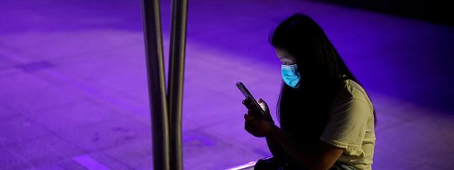 Eine junge Dame mit Maske und Handy in Wuhan