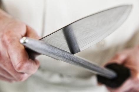 Messer wird mit Wetzstein geschliffen