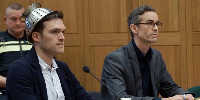 """Ein Mann sitzt neben seinem Anwalt im Gerichtssaal und trägt ein Nudelsieb am Kopf.  Filmszene aus """"I, Pastafari""""."""