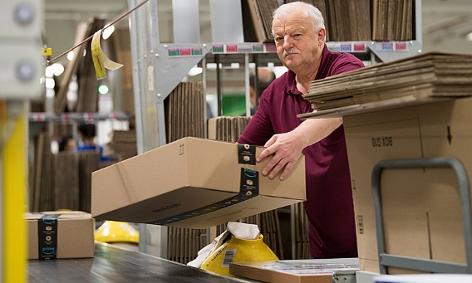 Mitarbeiter legt Amazon-Paket auf ein Transportband