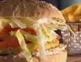 Veggieburger auf Holzbrett mit Pommes frites im Hintergrund
