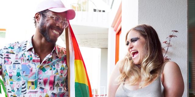 Menschen mit Regenbogenfahne bei der Fensterl Parade