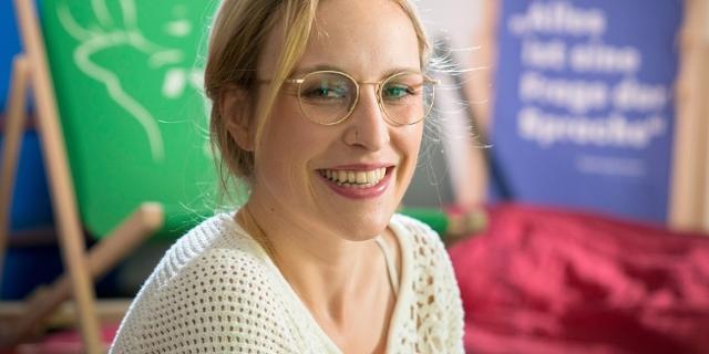 Hanna Herbst trägt Brille und Nasenring und freut sich