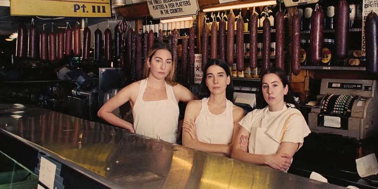 """Albumcover von Haims """"Women in Music Part III"""", in der die Band hinter einer Wursttheke steht."""