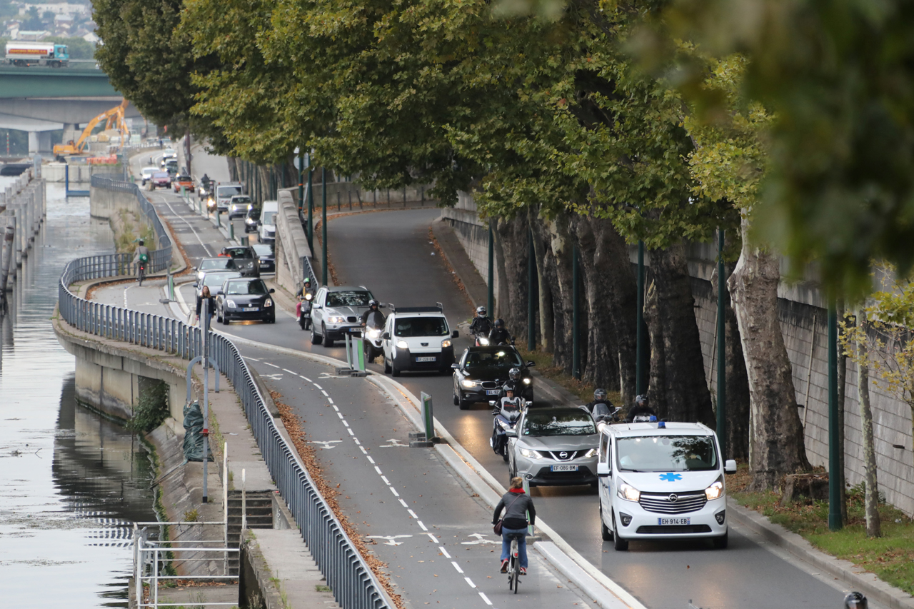 People ride their bicycles on the bicycle track past cars along the Seine River.