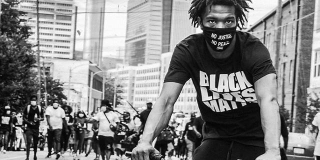 """Mann auf Fahrrad, auf dem T-Shirt """"Black Lives Matter"""", auf der Mund-Nasen-Maske """"No Justice - No Peace"""" im Hintergrund eine Demonstration"""