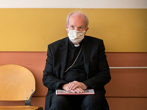 Kardinal Christoph Schönborn sitzt mit MNS und einer Mappe auf den Knien