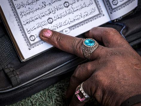 Eine Hand mit Ringen zeigt auf eine Stelle im Koran