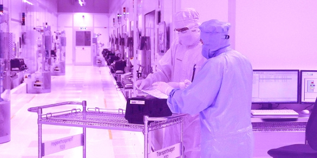 Mitarbeiter bei der Chip Produktion in einem Reinraum