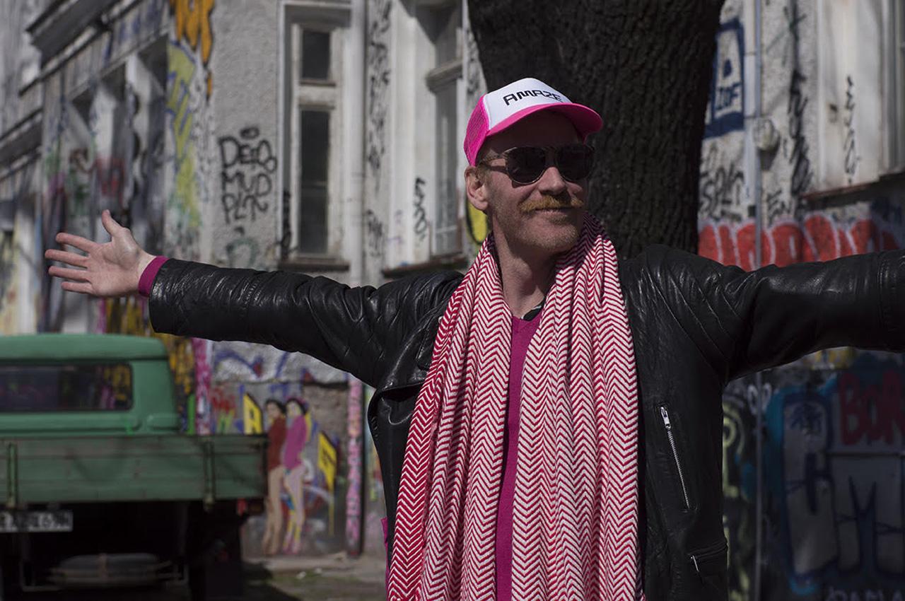 AMAZE Berlin Festivaldirektor Thorsten S. Wiedemann mit pinker Kappe und ausgestreckten Armen.