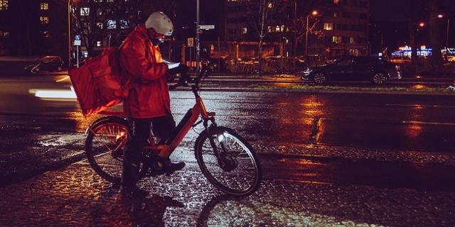 Fahrradkurier in der Nacht, schaut den Weg am Handy nach