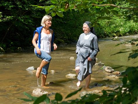 Zwei Frauen beim Wassertreten in einem Bach
