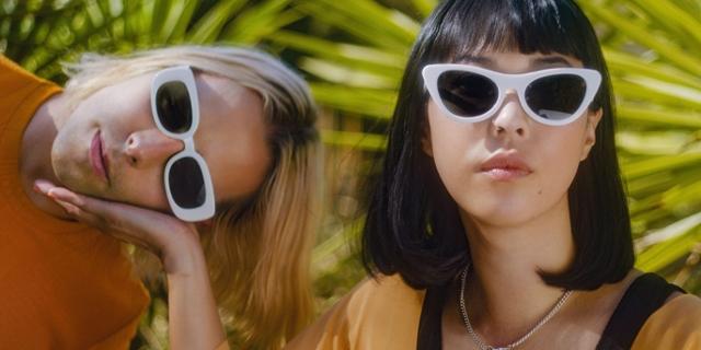 Alisa Xayalith hält Thom Powers' Kopf in ihrer Hand. Beide tragen Sonnenbrillen mit weißem Rahmen.