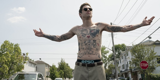 Mann mit vielen Tattoos steht mit ausgebreiteten Armen auf einer Straße