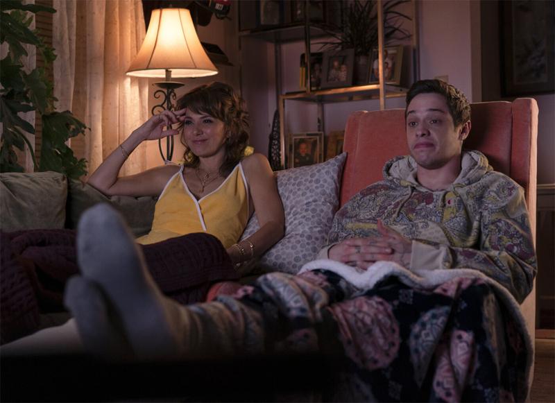 Eine Frau und ein Mann sitzen auf einem Sofa und schauen fern