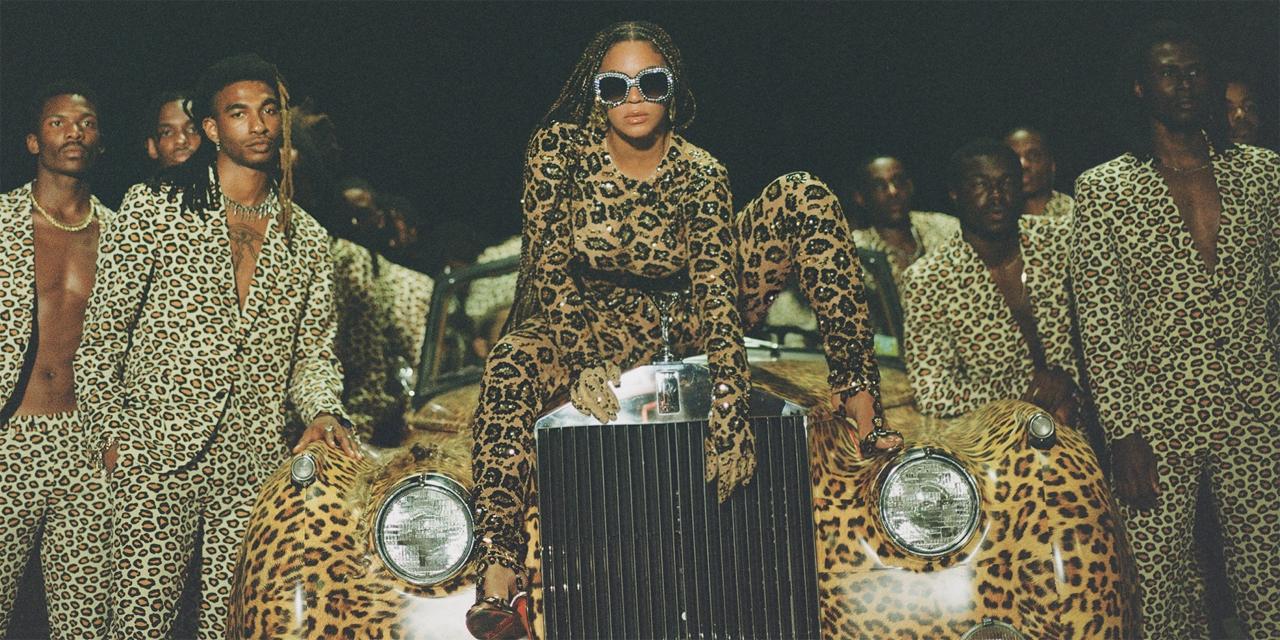 Beyoncé im Raubtierkostüm sitzt auf einem Luxusauto, umgeben von Schwarzen Männern
