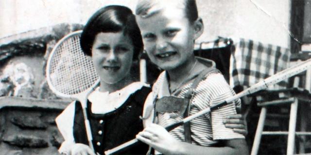 Schwarz-Weiß-Fotografie: Bub und Mädchen mit Tennisschlägern