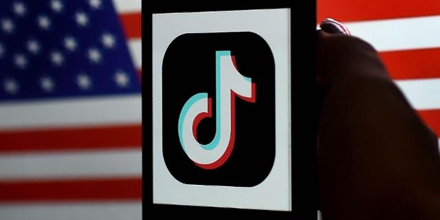 TikTok-Logo vor US-amerikanischer Flagge