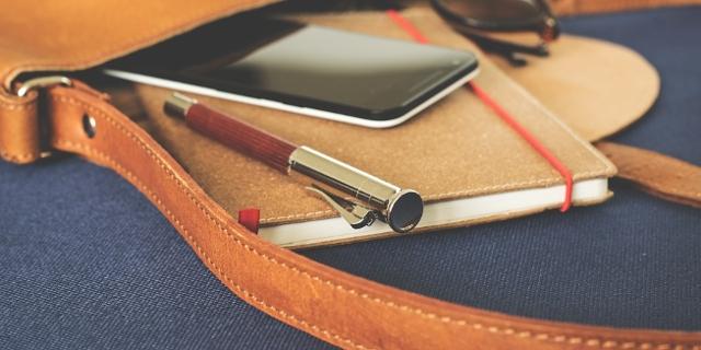 Leder Handtasche ausgeleert Inhalt: Handy, Notizbuch, Stift