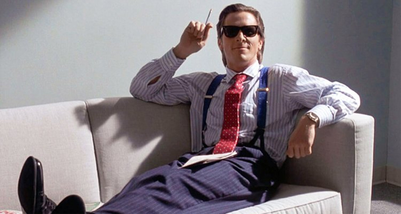 Christian Bale als Patrick Bateman liegt rauchend auf einem Sofa und grinst