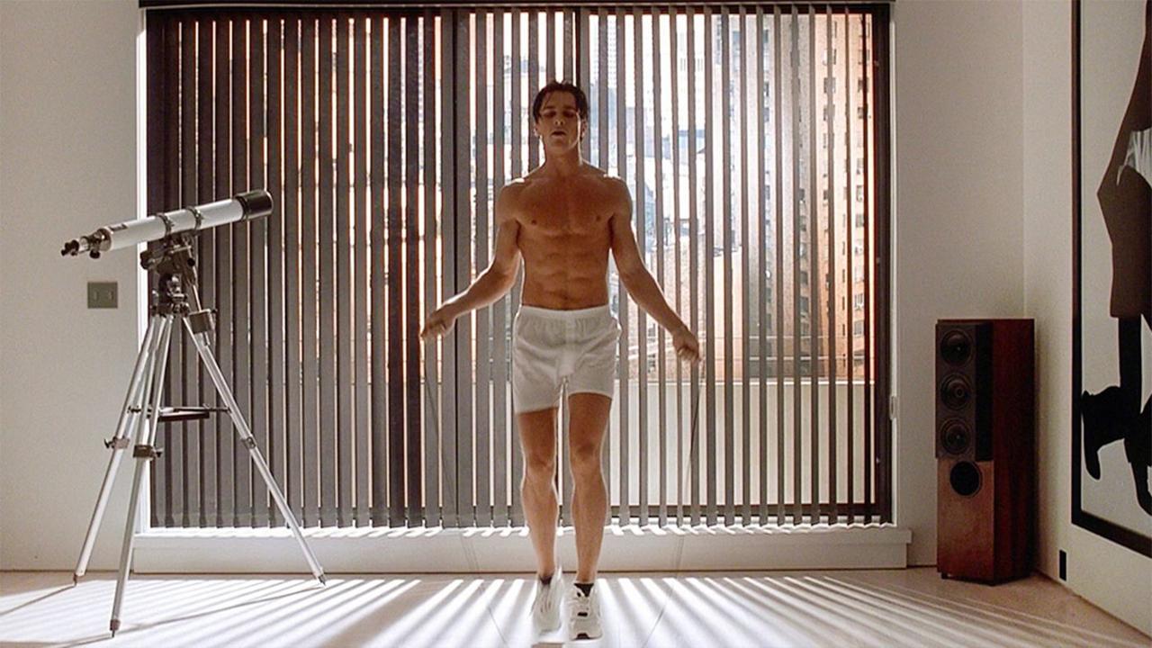Christian Bale als Patrick Bateman in Shorts beim Seilspringen in seinem Apartment
